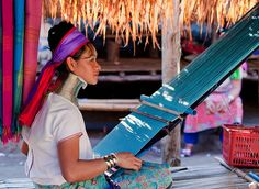 A Karen hill tribe woman hand weaves a scarf at her village near Chiang Mai