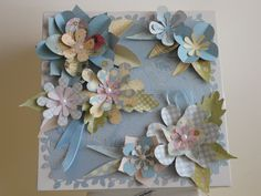 """I love to find the """"rejects"""" at Hobby Lobby...a bit of damage or wear.  This wooden box had some scratches on the top.  I covered the top with an embossed scrapbook paper using one of my edge punches.  Then I used the fun punch out flowers from K & Co. to further enhance the top.  I put a narrow satin ribbon around the cover edge.  It made a lovely gift for a lovely young lady."""