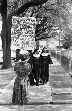 Two Roman Catholic  African American  nuns on Archbishop Joseph Francis Rummel's residence staff ignore a woman picket in front of the archbishop's home in New Orleans on April 23, 1962. Mrs. Delphine Roberts carried the sign protesting the archbishop's excommunication of three Catholics who defied his order to desegregate Catholics schools next fall. (AP Photo and Caption)