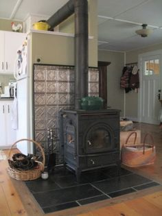 We would love to have a wood stove in our kitchen. They used tin ceiling tiles as heat shield for wood stove or pellet stove. Maybe this would be a way for me to incorporate tin tiles. Wood Stove Surround, Wood Stove Hearth, Stove Fireplace, Wood Burner, Wood Stove Heat Shield, Wood Stove Wall, Fireplace Hearth, Metal Building Homes, Building A House