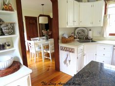 White Kitchen Reveal.  White painted cabinets and furniture with unpainted wood trim.