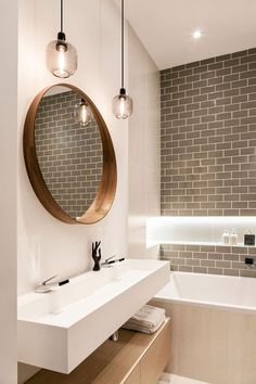 Grey tiles juxtaposed with white walls and plenty of lights (from pendents to spotlights) really enhances the space of this small bathroom.