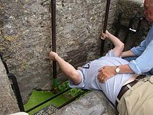 Ireland -- Visitor kissing the Blarney Stone, a block of bluestone built into the battlements of Blarney Castle, Blarney, about 5 mi. from Cork. According to legend, kissing the stone endows the kisser with the gift of the gab. The stone was set into a tower of the castle in 1446.