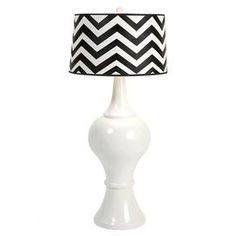 "Curved white table lamp with a chevron-printed shade.       Product: Lamp  Construction Material: Resin, polymer and iron  Color: Black and white    Features:   Bold chevron print Drum shade    Accommodates: (1) 60 Watt bulb or (1) 13 watt CFL type A bulb - not included    Dimensions: 49"" H x 22"" Diameter"