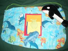 Under the sea bag front. Bags for foster kids made from pillowcases and stuffed with a furry friend. Project information can be found at: http://www.vagrimaldi.com/SewingProject.htm