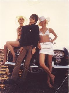 Keith Richards and two young ladies posing in front of a Rolls Royce.