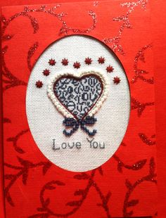 """Valentine Card for my husband 2014. I stitched the design for the center of the card & cut the oval out with Spellbinders oval die. Repeated cut out oval in specialty cardstock & applied to front of plain red CS with double-sided tape. Applied acetate to inside of plain red CS to protect cross stitched design. This was really fun to make! The cross stitch pattern in the center is from JBW Designs. If you look closely you will see """"love"""" spelled inside the heart. The embellishment is mine."""