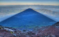 This jaw-dropping shot shows a shadow 15 miles long.  The distinctive dark triangular shape has been cast by Mount Fuji, Japan's highest mountain at 3,776 metres high.  Kent photographer Kris J Boorman captured the amazing image from the mountain's summit on a visit there two years ago.  The 28-year-old's photograph, which he took at sunrise around 5am, has now garnered international praise after he posted it online on Reddit last week. This was actually Kris' second attempt at capturing the…