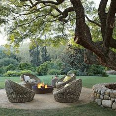 This wicker furniture looks so welcoming. I'd probably mix it up with a few different furniture pieces. I love the large tree in the background too!