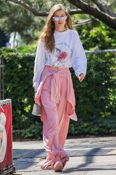 Gigi Hadid in an Adam Selman graphic long sleeve tee and pink trousers with pink Reebok sneakers, Stalvey bag and Le Specs x Adam Selman cat eye sunglasses while out in New York.