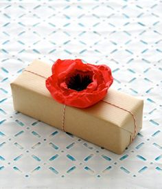 A pretty DIY poppy blossom for a gift wrapped in classic brown butcher paper. #diy #papercrafts