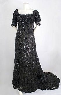 Beaded tulle evening gown, c.1910. In the scintillating evening gown, the elegant style molds to the torso, ending with a dramatic sweeping train. The outer black silk tulle layer is totally covered with a brilliant textural composition. The textured black-on-black design adds a layer of glamour to the languid Edwardian elegance. The ingenious combination of black glass beads, paillettes, and sequins is enhanced by creatively placing clusters on edge, producing a glittering three-dimensional…