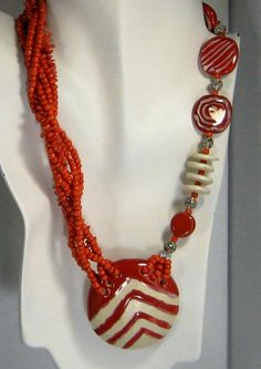 Red and cream Kazuri  bead  bead necklace. An asymmetric design showcases this red bead necklace.  The Kazuri beads used in this red necklace are fair trade products from Kenya.