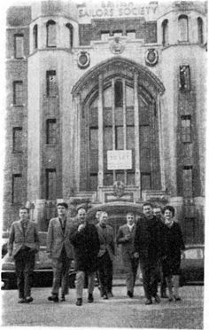 """Situationists at the Sailors' Society in London during the 4th Conference of the Situationist International. Those assembled included (from l. to r.): Attila Kotányi, Hans-Peter Zimmer, Heimrad Prem, Asger Jorn (covered), Jørgen Nash (front), Maurice Wyckaert, Guy Debord, Helmut Sturm, and Jacqueline de Jong. To ensure that the proceedings were kept away from any contact with artistic circles or London newspapers, the conference took place in Limehouse, """"a district renowned for its…"""