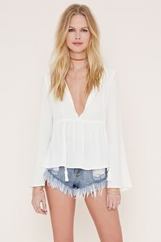 This crepe woven top features a tasseled self-tie slit plunging neckline with a crochet-trimmed open back cutout, a shirred waist, and long sleeves.