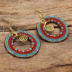 Orecchini di cotone cerato con a forma di ottone evidenzia nei toni del blu e rossi