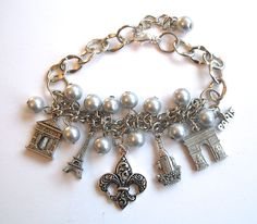 This great bracelet features your favorite Paris landmarks in silver pewter tones with dove grey pearls. From It's All About Paris