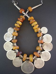 AntiqueMoroccan Berber Amber Necklace      A precious necklace of 11 Berber silver disks with niello spiral design symbolising eternity and genuine antique fossil Amber of beautiful tones and patina with the largest amber bead being 20mm. Lots of oldTuareg silver spacers and end beads with silver hook. A truly exceptional treasure of a necklace!