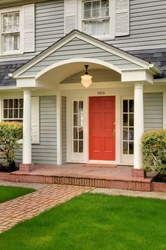 Red-orange door with light gray siding and white shutters, arched portico, brick walkway. Posted on Houzz by McCall Design in Portland, OR. Photo by Stephen Cridland Photography. Try BM Nimbus Gray or Palladian Blue and Outrageous Orange door. Dutch Colonial Exterior, Colonial Front Door, Colonial House Exteriors, Dutch Colonial Homes, Exterior Front Doors, Brick Porch, House Front Porch, Front Porch Design, Brick Walkway