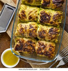 rolls of cabbage and meat baked in the oven with parmesan cheese. on a wooden table
