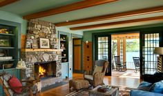 living room with blue-green walls, honey colored wood paneling/beams & a stone fireplace - Smith & Vansant Architects - G.R. Porter & Sons, Custom Builders