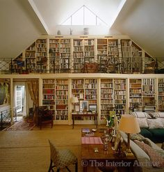 A wall of bookshelves dominates this former artists studio with a mezzanine floor which acts as a reading area and study