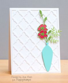 The Meso Background was cut out of white cardstock and attached to a white cardstock base. The Wild Rose Bud was cut several times, out of green and coral-pink cardstock. A sprig of greenery was added to the bouquet in the Tall Vase...