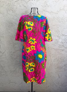 The show-stopping psychedelic 1960s dress is perfect for summer. Made in Hawaii by Royal Hawaiian, this dress is not for wallflowers. It would look stunning with some strappy wedges and of course a tropical drink!  The bust measures 36 from armpit to armpit. The total length is 36. The sleeves are flared and measure 12.5 long and 9.5 at their widest. A zipper in the back allows for easy wear. This dress is really flattering and is in perfect condition with no rips, stains or weird smells…