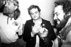 """Country singer Willie Nelson shares a joint with actor John Belushi as he pinkie swears with a Hells Angel at the Lone Star Cafe. New York City, circa 1980."""