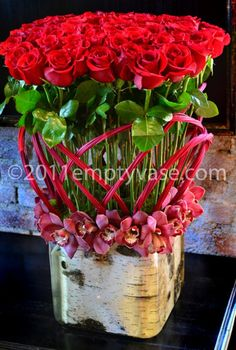 """ROSES AND BIRCH by Empty Vase 100 delicious red roses in a 10""""x10"""" rounded square vase lined with cymbidium orchids and decorative birchwood."""