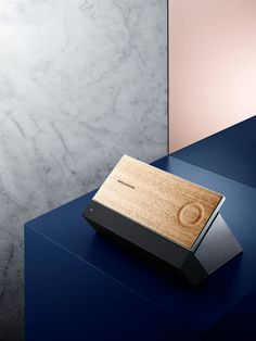 . Bang & Olufsen aims to reclaim the concept of a single-purpose device dedicated to music, the BeoSound Moment. It takes the form of a two-sided tablet, with the rear side constructed from wood (oak, to be specific). On the right side is a circular indentation. Tap the center of the wheel, and music immediately starts to play; drag your finger around the circular indentation and the volume will adjust accordingly.