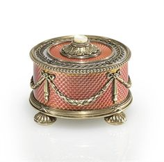 A Silver-Gilt and Guilloché Enamel Bell-Push Marked Fabergé, with the workmaster's mark of Hjalmar Armfelt, St. Petersburg, circa 1890, scratched inventory number 11693  Circular on four gadrooned bun feet, enameled in translucent salmon pink and white over a wavy guilloché ground, the top applied with a laurel border set with rosettes, centering a mother-of-pearl push-piece within an acanthus surround, the sides applied with ribbon-tied laurel swags, within beaded and ribbon-tied reeded…