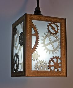 Multi-layered panels with cut gear designs give this hanging lamp a fun steampunk feel. Distressed gold-paint filigree inlayed into dark wood panels gives the outside a warm, worn look. Behind the diffusion, translucent acrylic gears are lit from behind, adding depth to the design as light passes through the sides of the lamp.