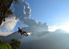 """""""End of the World"""". This photo, taken at the """"end of the world"""" swing in Banos, Ecuador, captures a man on the swing overlooking an erupting Mt. Tungurahua. The eruption took place on February 1st, 2014. Minutes after the photo was taken, we had to evacuate the area because of an incoming ash cloud. Photo location: Banos, Ecuador. (Photo and caption by Sean Hacker Teper/National Geographic Photo Contest)"""
