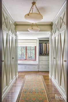 The desin team reworked the master closet as an extension of the master bedroom. The space is flooded with sunlight and features doors with an X detail that supply the space with a traditional sensibility. Simply furnished, it has Vaughan pendants and a Khotan runner from Christiane Milinger. | Designed by Joelle C Nesen, Maison Inc. | Photographed by David Papazian