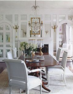Spectacular dining room with mirrors reflecting the light from the sconces and chandelier.