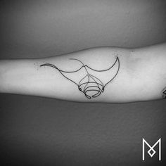 Continuous line manta ray tattoo on the right inner forearm.