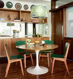A madeira presente nas estantes, nos móveis e no chão faz desta sala de almoço um lugar acolhedor e convidativo. Criado pela designer de interiores Marina Linhares para uma família com crianças, o espaço conecta-se à cozinha por meio de um visor