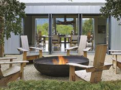 A collection of graphic updated Adirondack chairs surround an Indian cooking pot-turned-firepit. In summer, wisteria and grape vines shade the gravel terraces.