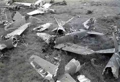 Dump of broken Japanese warplanes. In the foreground lying the wreckage of Mitsubishi A6M Zero fighter. In the background – Nakajima Ki-43 Hayabusa Single Seat Fighter.