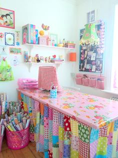 Super Kitsch Craft Room with patchwork curtain below the desk and oil cloth table top