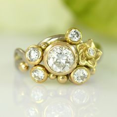 A bouquet of diamonds, centered around a large and perfect 1 carat diamond are gathered on this utterly stunning ring. Large and small bubbles of hot, 18k gold mingle on top of the twining white gold ring while a single flower nestles in amongst the glittering beauties. An utterly amazing princess ring with maximum bling factor!