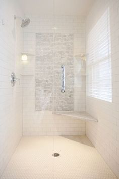 Stunning walk-in shower with a subway tiled interior and mini marble brick tiled accent panel flanked by corner shelves with rainfall shower head to the left and marble corner seat to the right over white mini hex tiled floors. Shower Accent Tile, White Subway Tile Shower, Subway Tile Showers, Shower Floor, Tiled Showers, Dream Shower, White Shower, Bathroom Showers, Shower Panels