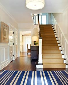 Clean white millwork stands out against the dark hardwood flooring, creating appealing contrast in this home's entry. A bold-striped area rug in white and blue add a pop of color to the space's neutral palette, while a brown carpet runner leads upstairs, softening the wood stairs.