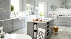 Grey and white kitchen with a kitchen island at the center. island books