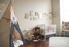 I love everything about this room: bird and branch mobile, dresses on display, window reading nook, and of course the teepee.