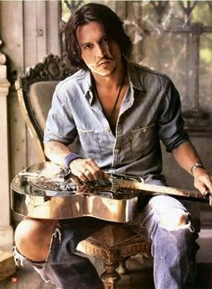 Johnny Depp. (It's not:ripped jeans/thug. It is:ripped jeans/artist. The open shirt with neckace is inviting as well)