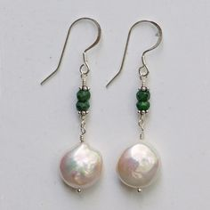 "Exceptional quality coin pearls are topped with faceted emerald beads, sterling silver french hook ear wires, 2"" long"