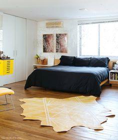 Quarto de casal tem cabeceira de madeira e roupa de cama preta.