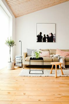 ChicDecó | Scandinavian living room in neutral palette; striped cushions; black side table; wooden stool; black and white artwork